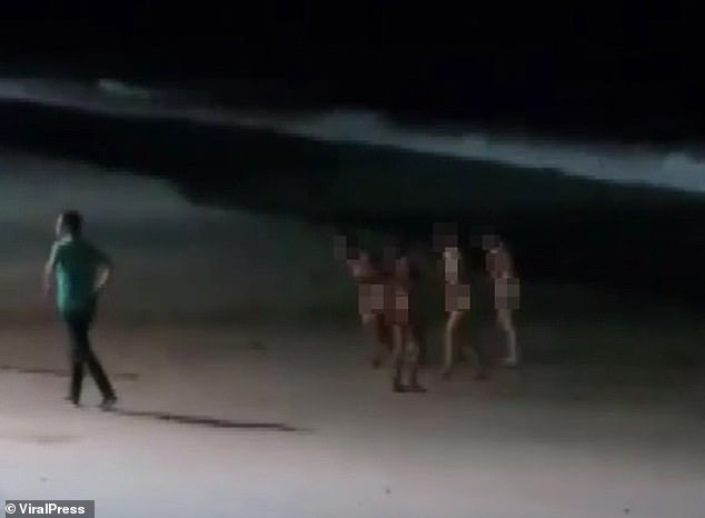 Some of the group can be seen making their way back up the beach on Monday night after they were discovered