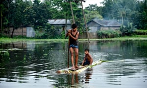 Indian children paddle a raft through floodwaters at Kalgachia in Barpeta district in India's northeastern state of Assam