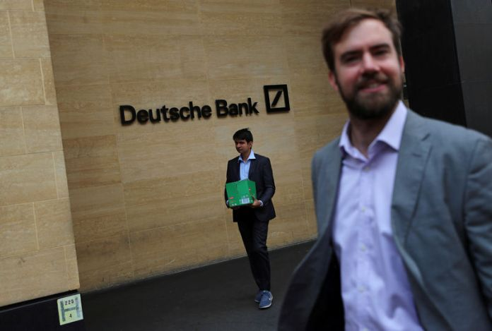 © Reuters. A man carrying a box leaves a Deutsche Bank office in London