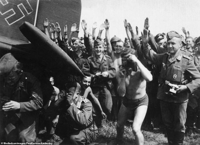 Greeting the Führer: Delighted pilots in the German Luftwaffe are about to meet Hitler in this photo, making the Nazi salute while several of them take pictures of their own. The photo was taken in August 1941 in Ukraine, when Hitler visited the occupied Soviet territory along with Italian dictator, and fascist ally, Benito Mussolini. At this stage, the German invasion of the Soviet Union was progressing as Hitler had hoped - but Stalin's forces would eventually turn the tide