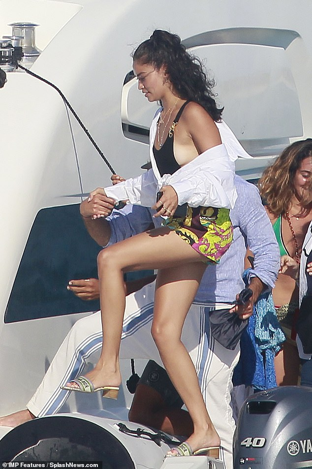 What a gent! The mystery friend then showed his gentlemanly side as he took Shanina's hand to help her aboard the yacht