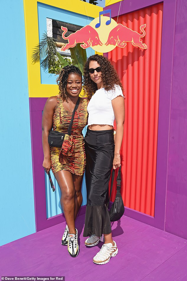 All smiles: Clara slipped into a red and yellow mini dress teamed with a pair of trainers as she posed for the cameras (pictured withSafia El Dabi)