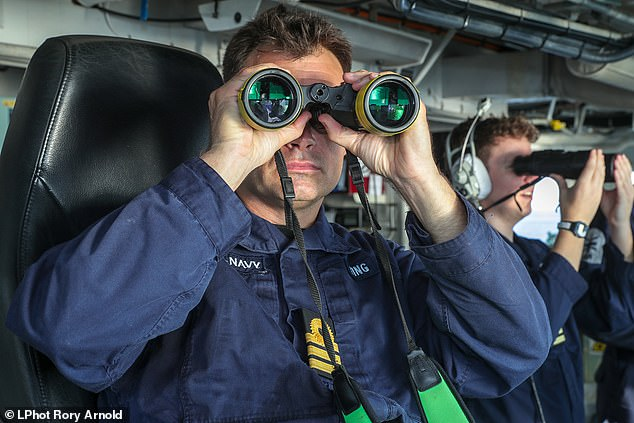 Commander of HMS Montrose Will King, 41, (left) looking through binoculars. Cdr Kings said: ¿You could almost hear the elation on their side. It was like a sick competition¿