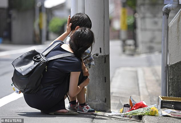 A mother and her child mourn for Yua Funato in front of the apartment where she died
