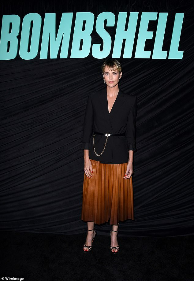 Burnt orange: The Mad Max star wore a black blouse with a burnt orange skirt for the screening