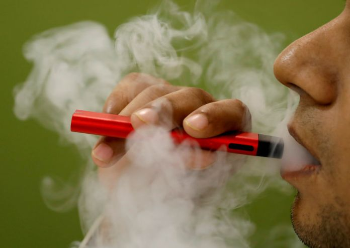 © Reuters. FILE PHOTO: A man uses a vape device in this illustration picture