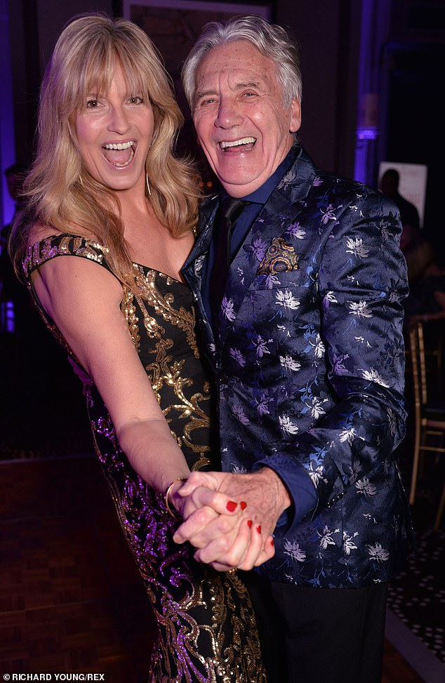 Well dressed: Penny also linked hands with fashion designer Jeff Banks, 76, who put on a flamboyant display in a metallic blue blazer