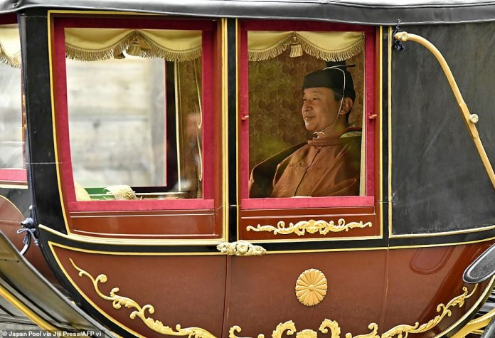 Japan's Emperor Naruhito sits in a carriage on his way to visit the outer shrine of the Ise Jingu Shrine in Ise, Mie Prefecture on November 22, 2019 to report the completion of major rites of his enthronement
