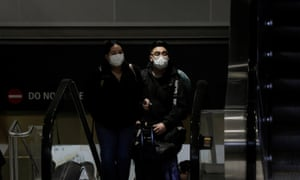 Travellers wearing masks arrive on a direct flight from China at Seattle-Tacoma International airport.