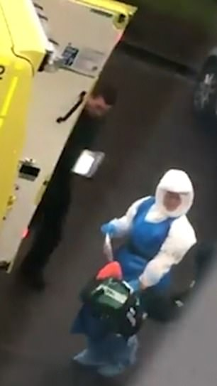 Two other paramedics wearing no protective clothing appear in the video - one comes from behind the ambulance doors