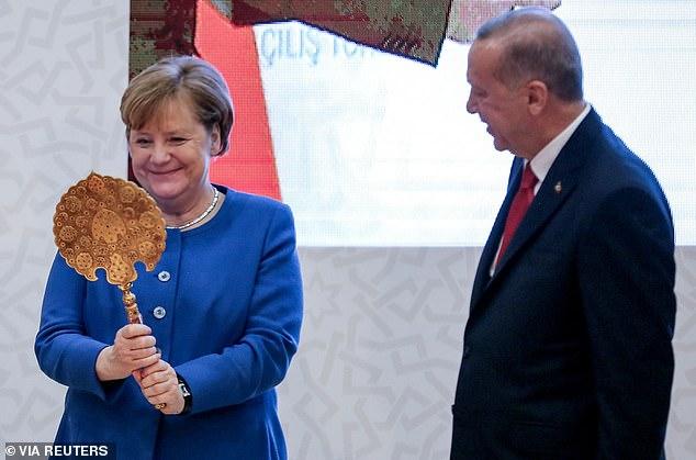 German Chancellor Angela Merkel receives a gift from Turkish President Tayyip Erdogan