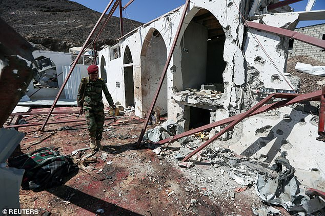 A Yemeni solider inspects the decimated scene on Monday. The death toll is expected to rise further with more than 60 other men wounded in the strike