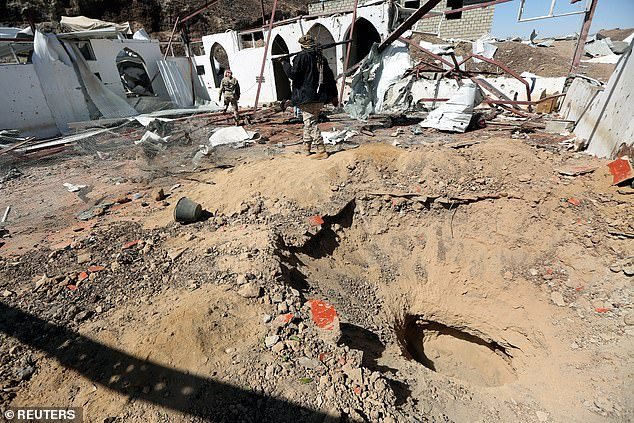 Government soldiers walk at the site of a Houthi missile attack on a military camp's mosque in Marib, Yemen on Monday