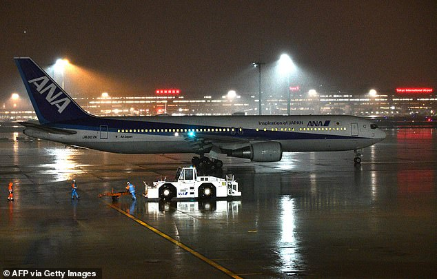 A charter plane organised by the Japanese government to evacuate nationals from Wuhan. It is pictured leaving Tokyo's Haneda International Airport passenger terminal this evening