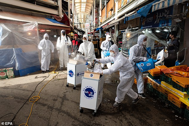 Workers spray disinfectant as a precaution against COVID-19 at Saemaeul traditional market in Seoul, South Korea, on 26 February 2020 - the same day that the first case of coronavirus where the origin of the disease is unknown was confirmed in the US