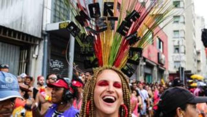 """A carnival-goer wears a headdress decorated with the phrase """"Love and Resistance"""""""
