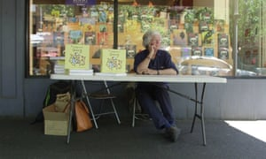leunig sits outside a bookshop at a signing table