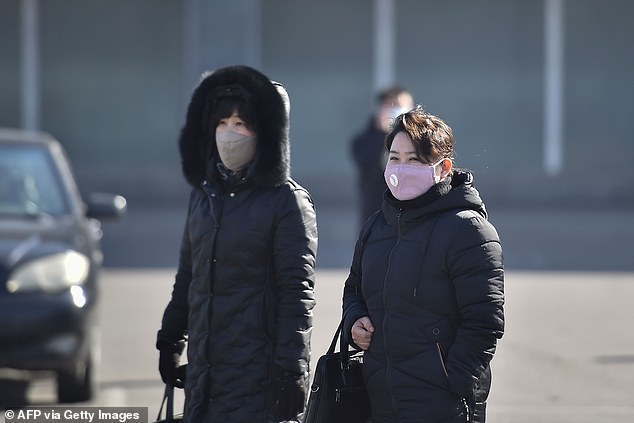 Officials in North Korea have been vigilant in isolating travellers from foreign countries and testing them for the coronavirus. Pictured, women wearing face masks in the capital city