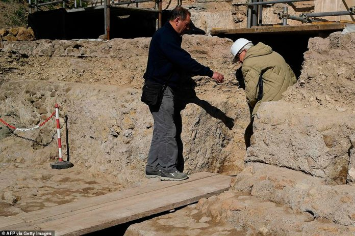 People stand by the access to an ancient tomb thought to belong to Rome's founder Romulus on February 21, 2020 at the Curia - Comitium in the Roman Forum of Rome