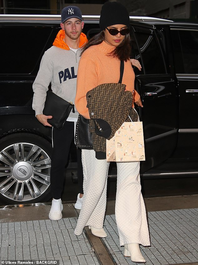 Staying warm:Priyanka paired her orange cream–colored turtleneck with flowing white waffle print pants and cream-colored boots