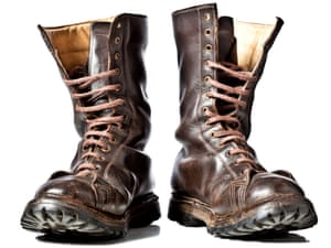 Used combat leather boots against white background