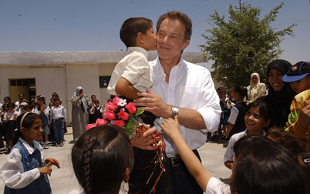 Prime Minister Tony Blair, receiving a kiss from schoolboy, Abbas Adnan, in Basra, Iraq, Thursday May 29, 2003. In calling for the war in the House of Commons in 2002, Blair stressed the potential for extensive damage to the Iraqi population from Saddam's 'weapons of mass destruction'