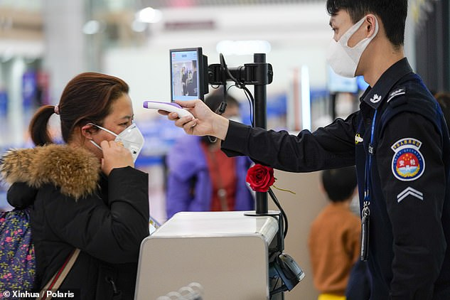 Originating in the central Chinese city of Wuhan, the new virus has infected more than 75,400 people inside China and 76,700 globally. In the picture above, a security staff member checks a passenger's temperature at Chongqing Jiangbei International Airport on January 26