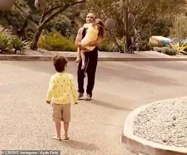 Cute: In the video Robbie ran to greet his two oldest children, Theodora, seven, and Charlton, five, after arriving at their LA home