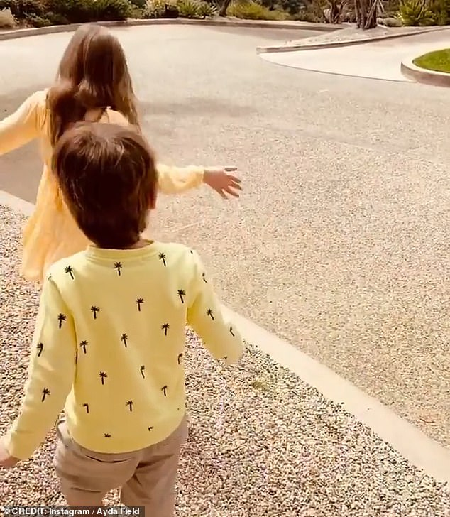 Look who it is! In the sweet video,Ayda asked her children who they could see walking up the driveway, with Teddy screaming in excitement 'Daddy!'