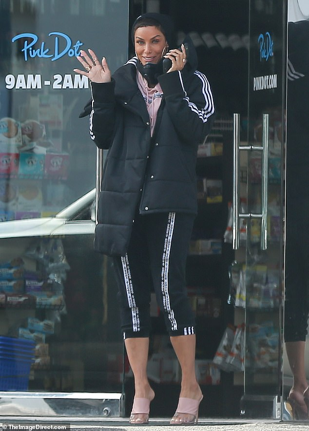 Adorable in Adidas: Nicole looked beautiful in her coordinated outfit, which consisted of a black beanie cap, a poofy black down coat, a pale pink hoodie, and black track pants