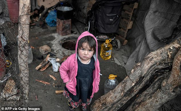 A child migrant stands in her family's shelter in Lesbos surrounded by rusted and discarded objects