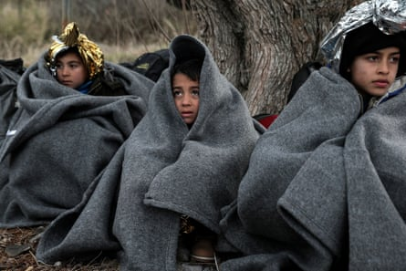Children huddle under blankets after arriving by dinghy on a beach on Lesbos.