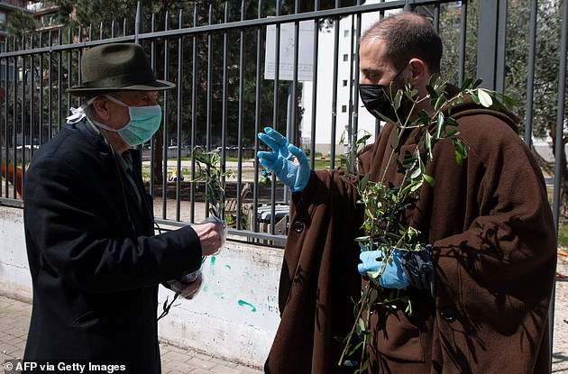 Parish priest Don Antonio Lauri blesses a resident's palm branch after celebrating Palm Sunday mass from the rooftop of the San Gabriele dell'Addolorata church in Rome on April 5