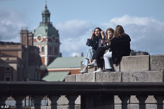 Young people socialise on a rooftop in Stockholm on Saturday. Officials in Sweden have so far refused to order a lockdown amid the coronavirus crisis