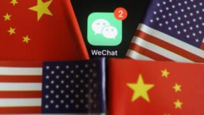 Messenger app WeChat is seen among U.S. and China flags