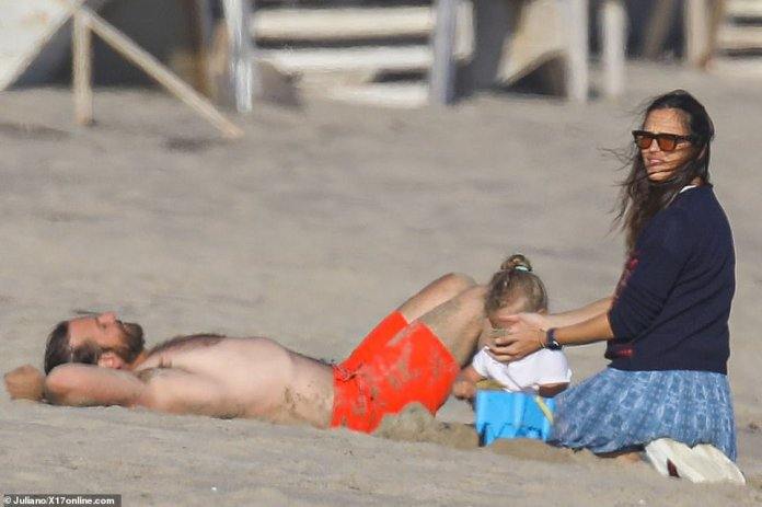 Building sandcastles: Jennifer, 48, played with Bradley's three-year-old daughter as he caught some rays