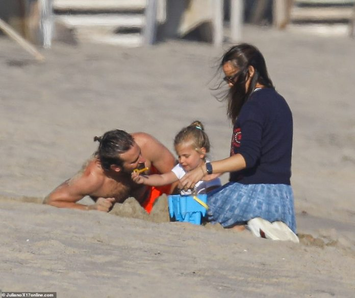 Family: Jen happily mucked in with family duties as she played with Bradley's daughter