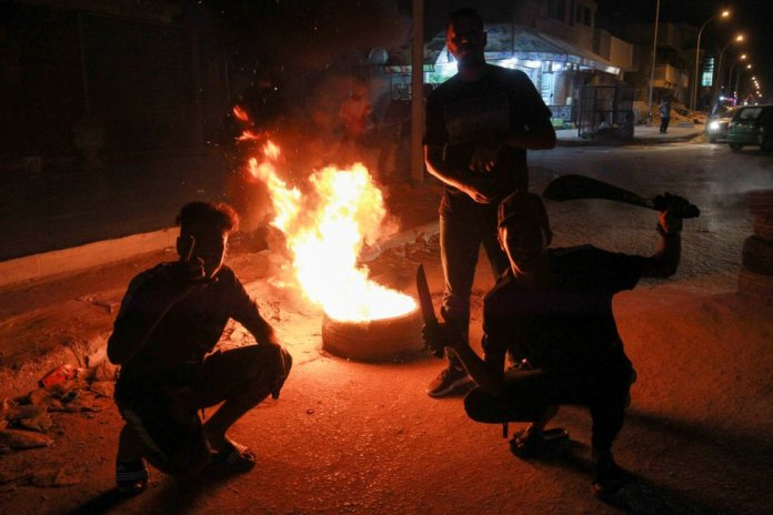 Young men block a road with burning tyres during protests in Libya's eastern coastal city of Benghazi on 12 September 2020.