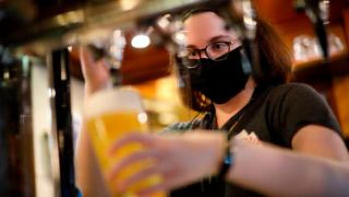 Member of bar staff wearing face covering