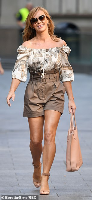 Leggy: She flaunted her tanned and toned pins in the belted shorts that perfectly matched her top