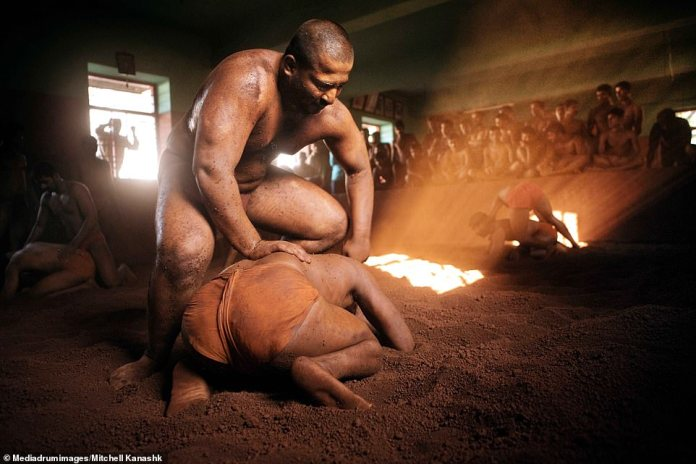 Kushti students perch with legs crossed watching more experienced wrestlers fight in the soil in front of them. A large wrestler pins his opponent to ground, kneeling on his back