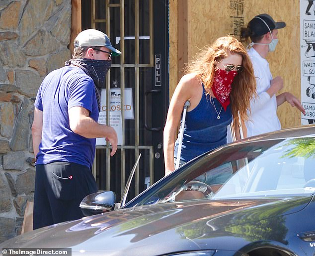 Ouch: Last month, Jon was ever the chivalrous boyfriend last month when opening the car door for her as she used a boot and crutches, appearing to have a foot injury