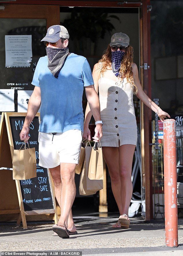 Goodies: The duo were first leaving a shop with bags in tow, with Jon wearing a blue shirt with shorts, adding a baseball cap, bandanna as a mask and flip flops