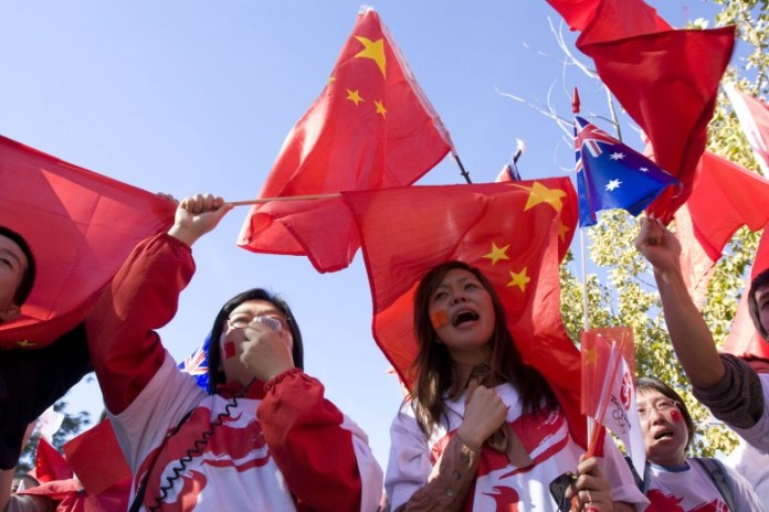 Chinese people wave Chinas and Australian national flags in Canberra, Australia in a file photo. Photo: AFP