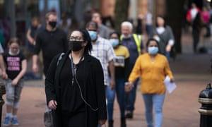 Pedestrians wearing face masks walk in the city centre of Birmingham.