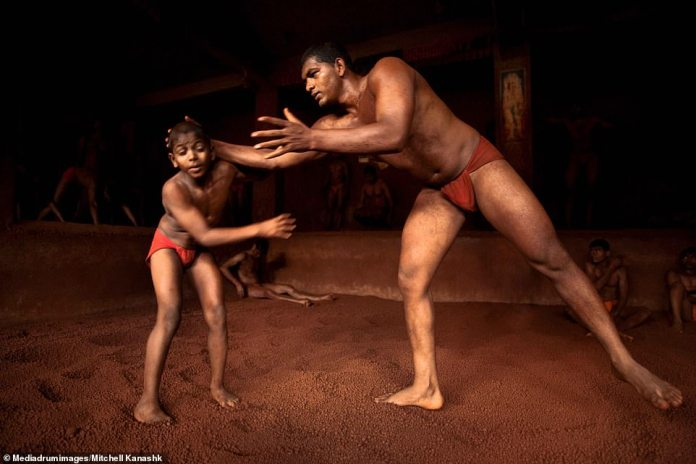 A young boy is taught a wrestling move by one of the adult men at a gym in Kolhapur.Some young boys are sent to learn discipline by their wealthy fathers