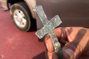 Artemio Guterrez, a single father of four, holds a cross made of two pieces of glass that melded together during the intense heat from the wildfire that swept through Talent, Oregon.