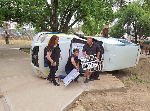 Demonstrators hold 'Boer Lives Matter' banners in front of an overturned police van outside the court in Senekal, Free State, on Tuesday
