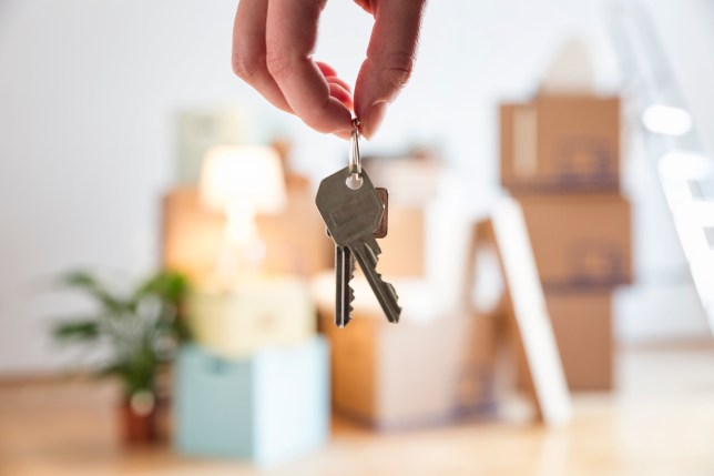 A hand holds keys to a new house, moving boxes are in the background.