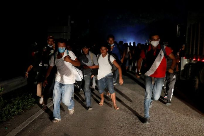 © Reuters. Honduran migrants trying to reach the U.S. run away after hurling stones to Guatemalan soldiers blocking a road to stop migrants from reach the Mexico's border, in San Pedro Cadenas